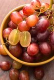 Close up red seedless grapes in a ceramic bowl. On a wooden table Royalty Free Stock Photo