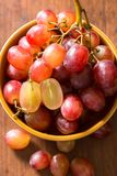 Close up red seedless grapes in a ceramic bowl on. A wooden table Stock Photos