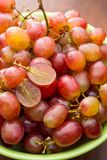 Close up red seedless grapes in a green ceramic bowl. On a wooden table Stock Photo