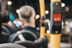 Close up of the red STOP button inside double decker bus in London. Passengers on the background Royalty Free Stock Image
