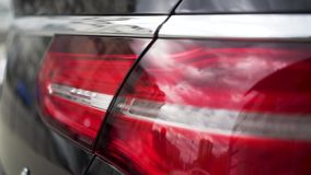 Close up of red tail lights, detail of modern, luxury, black SUV. Stock. Black car break lights, automotive lighting. Close up of red tail lights, detail of stock video footage