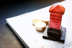 Close up red toy post box and money baht coin on the monthly planner calendar on black background. Summer calendar schedule. Calen. Dar scheduling for travel royalty free stock images