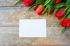 Close up of red tulips and blank paper or letter Stock Photo