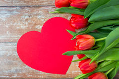 Close up of red tulips and paper heart shape card Stock Images