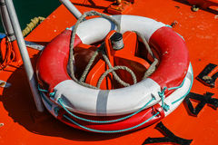 Close-up of a red and white weatherd life-belt (buoyancy aid) on. The deck of a fishing boat Royalty Free Stock Image
