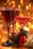 Close-up of red wine in glasses and candle. Close-up of red wine in glasses, green twig. candle light and bauble on blurred lights background Stock Image