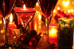 Close-up of red wine in glasses,candle and baubles. Close-up of red wine in glasses,candle lights,baubles,green twig and twinkle lights on background Stock Image