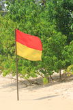 Close up of a red and yellow safety flag on an idyllic beach Stock Photography