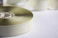 Close-up reel with a negative 35mm film. Copy space for announce. Ment of Films Stock Photos