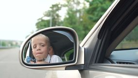 Closeup reflection in the side mirror in the car of a little boy with his mother. Close-up reflection in the side mirror in the car of a little boy with his stock footage