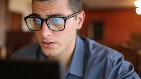 Close-up of reflections of laptop monitor screen in man`s glasses. Young caucasian freelancer businessman working and stock video footage
