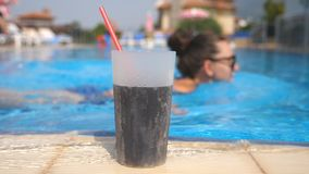 Close up of refreshing cocktail with straw standing near pool. Young girl in sunglasses swiming at background of glass stock video footage