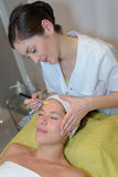 Close-up relaxed woman receiving therapy on forehead Royalty Free Stock Image