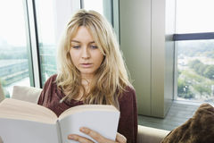 Close-up of relaxed young woman reading book in living room at home Royalty Free Stock Photography