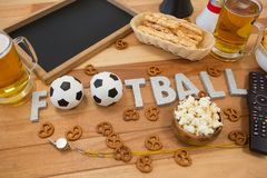 Remote control, slate, snacks, drinks and football word arranged on table. Close-up of remote control, slate, snacks, drinks and football word arranged on table Stock Image