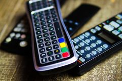 Close up of remote controls for TV, Video and stereo music system on wood table. Germany living room royalty free stock photos