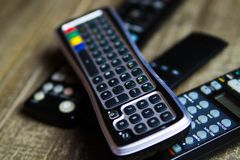Close up of remote controls for TV, Video and stereo music system on wood table. Germany living room stock photos