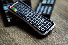 Close up of remote controls for TV, Video and stereo music system on wood table. Germany living room stock image