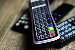 Close up of remote controls for TV, Video and stereo music system on wood table royalty free stock photography