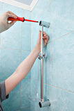 Close-up of repairman hands mounted on wall holder shower bracke Royalty Free Stock Photography