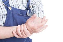 Close-up of repairman holdig his wrist in pain Stock Image