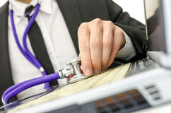 Close up of repairman holding stethoscope of laptop keyboard Royalty Free Stock Photo