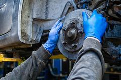 Auto mechanic repair. Close-up replacement of the old rear drum brakes on a car raised on a lift in a car repair shop. Auto mechanic repair stock image
