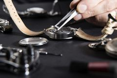 Detail of the work of a watchmaker who replaces a battery. Close up of replacing a watch battery with watchmaker tools royalty free stock photography