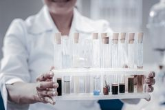 Close up of researcher holding set of test tubes. Experimental approach. Scaled up look on hands of a female scientist working in a lab and holding a set of test stock photo