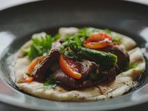 Close-up of a restaurant dish. Served cafe lunch on a blurred background. Grilled vegetables and meat steak on a bread. royalty free stock photography