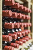 Close up of resting wine bottles stacked on wooden racks royalty free stock image