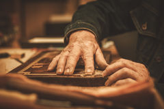 Close-up of restorer hands working with antique decor element in his workshop Royalty Free Stock Photography