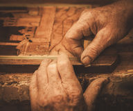 Close-up of restorer hands working with antique decor element in his workshop Stock Photo