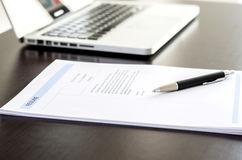 Close-up of resume, pen and computer laptop on black wooden desk Stock Images