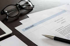Close-up resume, pen, digital tablet, eyeglasses and business ca. Close-up resume form, pen, digital tablet, eyeglasses and business card on wooden desk Royalty Free Stock Images