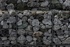 Close-up of a retaining wall made of stones. A wall called a gabion. Stone wall with metal grid as background. royalty free stock photo
