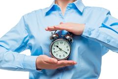 Close-up of a retro alarm clock in the hands of a businesswoman. In a blue shirt Royalty Free Stock Photos