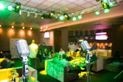 Close-up of retro microphone. Blurred club interior with unrecognizable people on background Royalty Free Stock Photo