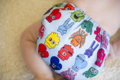 Close up of a reusable all in one nappy. A monster printed reusable cloth nappy on a baby boy stock photography