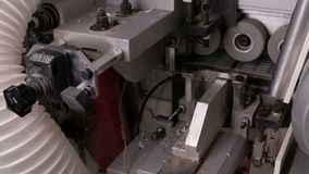 Close-up of the reverse side of the edge banding machine. Automatic gluing, trimming brown pvc edges and chamfering in furniture p. Close-up of the reverse side stock footage