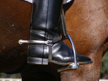 Close up of rider leg with spur. Close up of rider leg in the riging boot with spur and stirrup Royalty Free Stock Photo