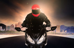 Close up rider man wearing safety suit and anti knock helmet rid. Ing big bike motorcycle on asphalt street against urban and sky scrapper building use for Royalty Free Stock Image