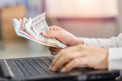 Close up right hand female with Euro banknotes and left hand using notebook. Calculation at home Stock Image