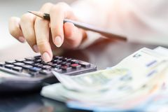 Close up right hand female using calculator in Euro banknotes background Royalty Free Stock Image