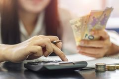 Close up right hand female using calculator and left hand hold with Euro banknotes Stock Photos