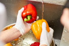 Close up rinsing two bell peppers. Stream of water falling on bell pepper. Washing bell peppers into sink Stock Photography