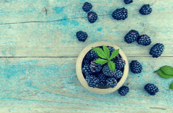 Close up of ripe blackberries over rustic turquoise wooden table. Top view royalty free stock photography