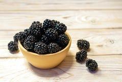 Close up of ripe blackberries in a white ceramic bowl over rusti stock photos