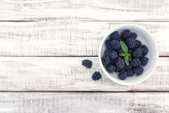 Close up of ripe blackberries in a white ceramic bowl over rustic wooden background stock images