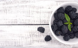 Close up of ripe blackberries in a white ceramic bowl over rusti Royalty Free Stock Images
